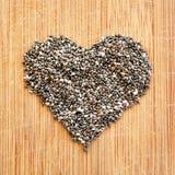 Chia Seeds arranjou no coração na placa de corte de madeira da grão, no formato quadrado para meios sociais, nas bandeiras e nos  Foto de Stock