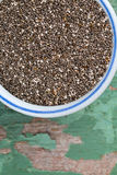 Chia seeds in a bowl on wooden surface Royalty Free Stock Images