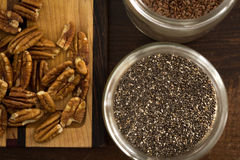 Chia seeds in container beside cutting board, pecans, flax seeds Royalty Free Stock Photos