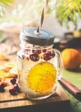 Chia seeds detox water. Healthy beverage with orange fruit slice , lemon juice and cranberries in glass jar and drinking straw on. Kitchen table with royalty free stock photos