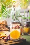 Chia seeds detox water with orange fruit slice , lemon juice and cranberries in glass jar with drinking straw on kitchen table. With ingredients. Summer drinks stock images