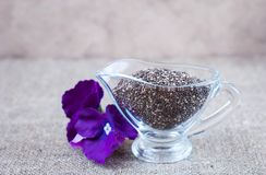 Chia seeds in glassware with purple flowers on a linen tablecloth. In a rustic style Stock Photos