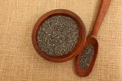 Chia Seeds Inside Wooden Bowl och sked Royaltyfri Bild
