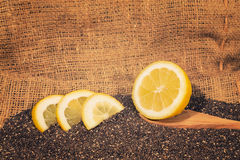 Chia seeds with lemon slices. A healthy source of antioxidants, omega 3 and fiber with wooden spoon in a burlap Royalty Free Stock Photo