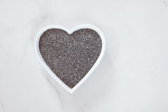 Chia seeds. Raw whole  chia seeds in a hearts shaped dish. Natural light Stock Photos