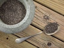 Chia seeds. Rough stone bowl  filled with black and white chia seeds with a spoon against aged knotted wooden background Royalty Free Stock Images