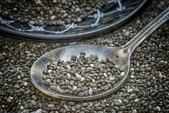 Chia seeds Salvia hispanica with metal spoon. On many seeds spread out royalty free stock image