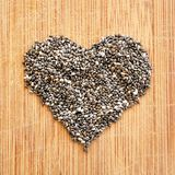 Chia Seeds som är ordnad i hjärta på den wood kornskärbrädan, det fyrkantiga formatet för socialt massmedia, baner och bakgrunder Arkivfoto
