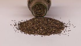 Chia seeds spilling of glass jar on white background Royalty Free Stock Photos