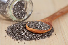Chia seeds spilling out of glass bottle on table Royalty Free Stock Photos