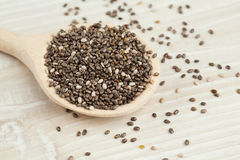 Chia seeds in a spoon on wooden surface. Background stock image
