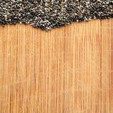 Chia Seeds sul tagliere di legno del grano, sul formato quadrato per i media sociali, sulle insegne e sul fondo Immagini Stock