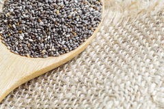 Chia seeds, super food, in wooden spoon on burlap background Royalty Free Stock Photo