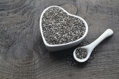 Chia seeds in a white heart shaped bowl on old wooden background.Salvia hispanica seeds. Healthy food or superfoodnconcept.Selective focus stock photos