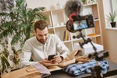Chiacchierando con gli abbonati Blogger maschio di modo che risponde sulle domande dopo online il flusso continuo per il suo blog immagini stock