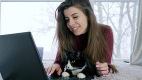 Chiacchierando in Internet, bella signora con l'animale domestico davanti al computer portatile video d archivio