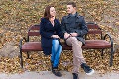 Chiacchierata di seduta delle giovani coppie amorose su un banco Immagine Stock Libera da Diritti