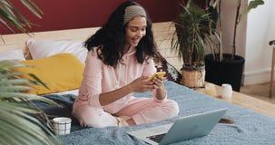 Chiacchierata e invio di messaggi di testo afroamericani felici della ragazza sullo smartphone che si siede sul letto a casa La g archivi video