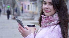 Chiacchieri su Internet, femminile con lo smartphone ed il vetro di caffè comunica al primo piano degli amici all'aperto
