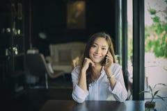 Chiamata asiatica della donna con il telefono delle cellule mentre sedendosi da solo nella c Fotografie Stock Libere da Diritti