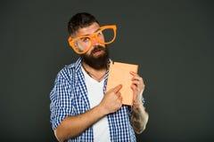 Chiamata dell'attenzione al suo manuale Nerd del libro che indossa i vetri operati Uomo barbuto in vetri del partito con il libro fotografia stock