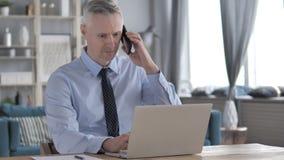 Chiamata di Gray Hair Businessman Attending Phone mentre lavorando al computer portatile archivi video