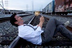 Chiamata di telefono delle cellule sulle piste del treno Immagini Stock