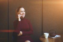 Chiamata femminile attraente con il telefono cellulare mentre aspettando il suo ordine al ristorante Immagini Stock Libere da Diritti