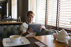 Chiamata femminile sorridente dei giovani in cuffie via collegamento a Internet sul suo cuscinetto di tocco Immagini Stock Libere da Diritti