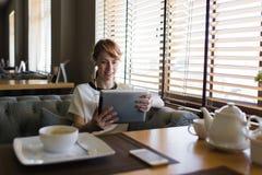Chiamata femminile sorridente dei giovani in cuffie via collegamento a Internet sul suo cuscinetto di tocco Fotografia Stock