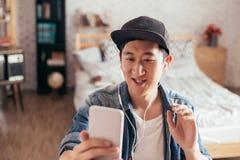 Chiamata video di conversazione del giovane uomo asiatico felice tramite cuffie d'uso dello smartphone a casa Immagini Stock