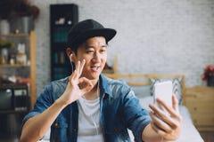 Chiamata video di conversazione del giovane uomo asiatico felice tramite cuffie d'uso dello smartphone a casa Immagine Stock Libera da Diritti
