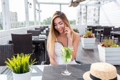 Chiamate allegre della ragazza sul telefono, caffè di estate, aria fresca sulla veranda Vetro di cocktail bianco del vestito dall fotografie stock libere da diritti