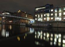 chiamate che atterrano sul fiume Aire a Leeds alla notte con le luci di vecchie costruzioni storiche e gli appartamenti riflessi  fotografia stock