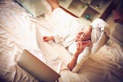 Chiamate di affari di mattina dal letto Donna immagine stock