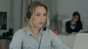 Chiami l'operatore che riempie nei dati del cliente sul suo computer portatile nell'ufficio Fotografie Stock