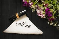 Chiamimi iscrizione su un tovagliolo su un fondo scuro di legno Fotografia Stock Libera da Diritti
