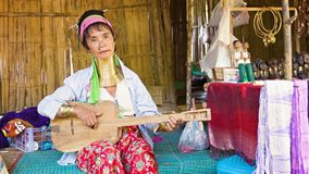 CHIAND RAI, THAILAND: Kayan Lahwi (Long-Necked Kayan) woman with neck rings play wooden guitar in hill tribe village. CHIAND RAI, THAILAND - 04 DEC 2013: Kayan stock footage