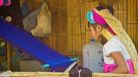 CHIAND RAI, THAILAND Kayan Lahwi (Long-Necked Kayan) woman with neck rings spin blue yarn in hill tribe village. stock footage