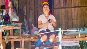 CHIAND RAI, THAILAND: Kayan Lahwi (Long-Necked Kayan) woman with neck rings spin yarn in hill tribe village. stock footage