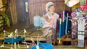 CHIAND RAI, THAILAND: Kayan Lahwi (Long-Necked Kayan) woman with neck rings spins yarn in hill tribe village. CHIAND RAI, THAILAND - 04 DEC 2013: Kayan Lahwi ( stock footage