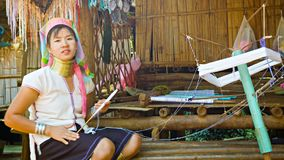CHIAND RAI, THAILAND: One Kayan Lahwi (Long-Necked Kayan) woman with neck rings spin yarn in hill tribe village. stock video