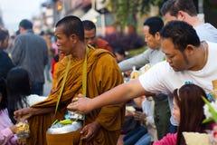 CHIANG KHAN THAILAND - Januari 1, 2015: Turistofferingsmat till munkar Arkivfoto
