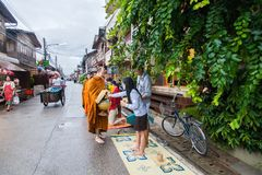 Ourists offering sticky rice to Buddhist monk the morning Royalty Free Stock Image