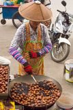 Thai woman preparing roasted chestnuts on the street royalty free stock photo