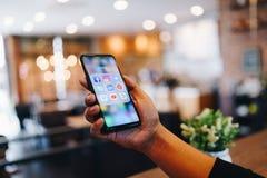 CHIANG MAI, TAIL?NDIA - mar?o 24,2019: Homem que guarda a mistura 3 de Xiaomi MI com ?cones de meios sociais na tela Os meios soc imagem de stock
