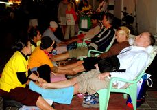 Chiang Mai,TH: Foot Massage Spa. Western tourists sitting in plastic chairs at an outdoor spa enjoying a traditional Thai foot massage at the Walking Street Royalty Free Stock Photo