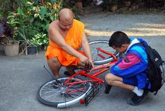 Chiang Mai, TH: Monk Fixing Bicycle Royalty Free Stock Photography