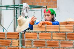 Female construction worker stacks terra cotta bricks to make wal royalty free stock photos