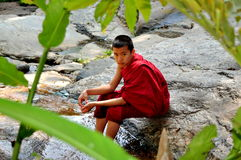 Chiang Mai, Thailand: Boy Monk Sitting on Rock Stock Photo